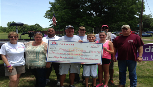 Group of adults and children with a check.
