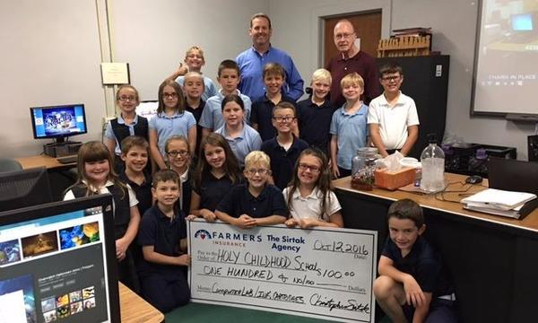 Presenting a check for $100 to the computer lab at Holy Childhood School, Mascoutah, Il
