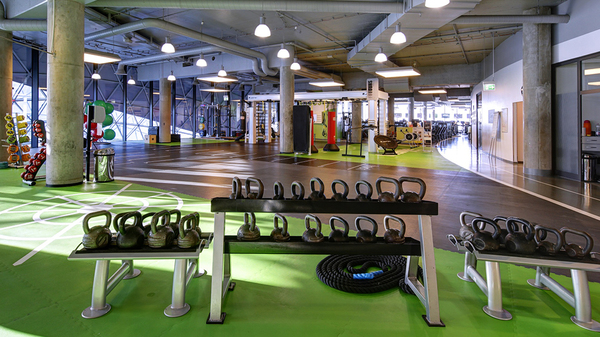 Inside a Fitness First Location, with bright green mats, racks of kettlebells of all sizes, a coiled battle rope and more exercise equipment in the background.