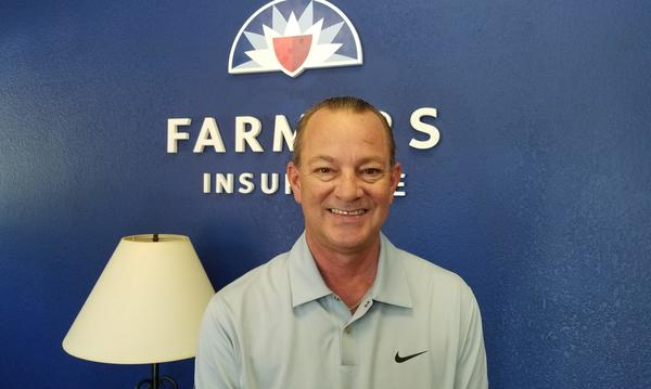 Staff member Phillip Jarnagin, standing in front of a wall featuring the Farmers Insurance logo.