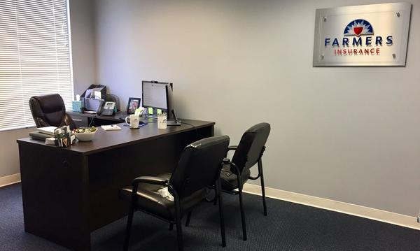 Two chairs in front of a desk next to a Farmers Insurance® plaque