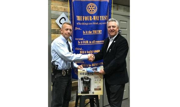 Agent shaking hands with a Police chief in front of a Rotary Club banner