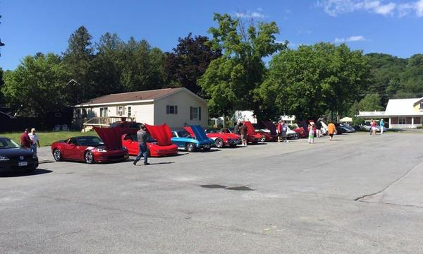 Photo of classic cars lined up with their hoods open.