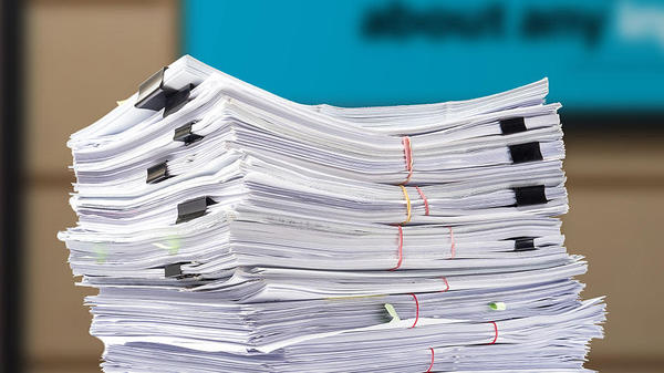 a stack of documents secured with paperclips and rubberbands