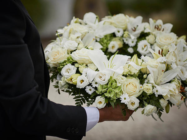 A white funeral wreath held by an arranger