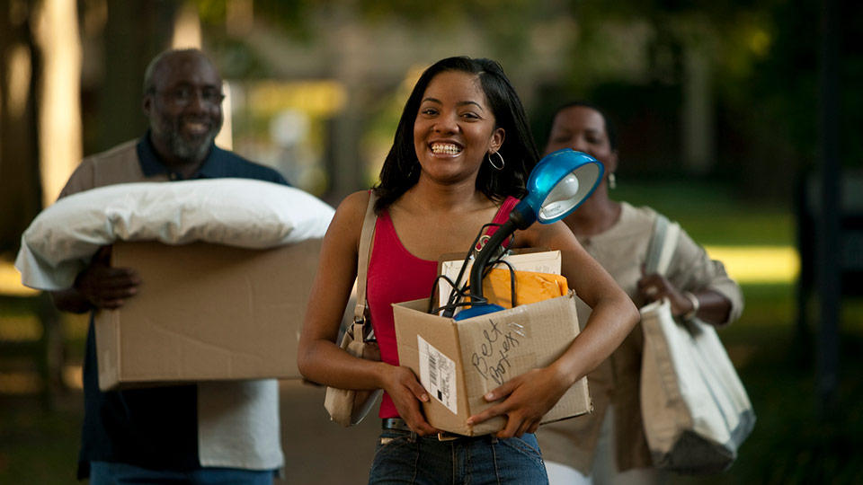 A smiling student carries a box from her dorm with her parents carrying boxes behind her.