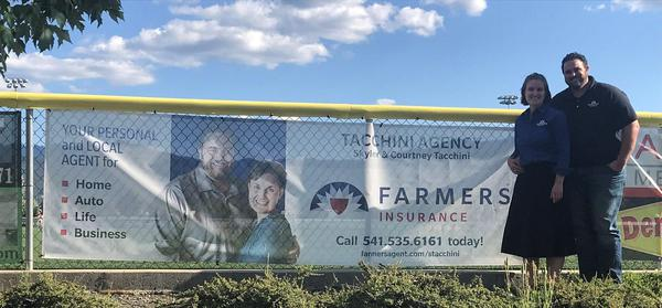 Agents standing with their banner at a sports field