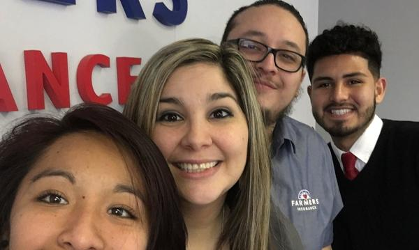 Agent and three staff members standing in a line in front of the Farmers Insurance logo
