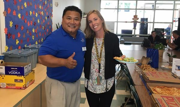 Agent Glenn Domingo giving a thumbs up to the camera, posing with a woman holding a piece of pizza, in a school cafeteria.