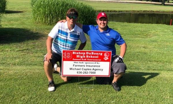 Two adults posing for a photo next to a Farmers sign at the High School's golf tournament.
