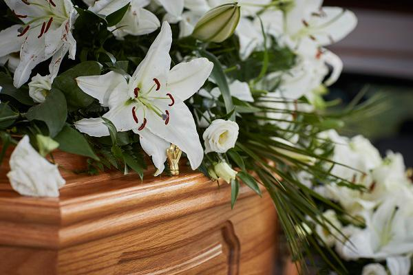 Funeral flowers placed on coffin lid
