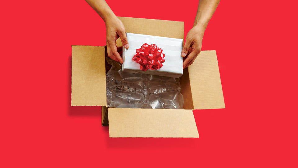 Gift being placed into a shipping box