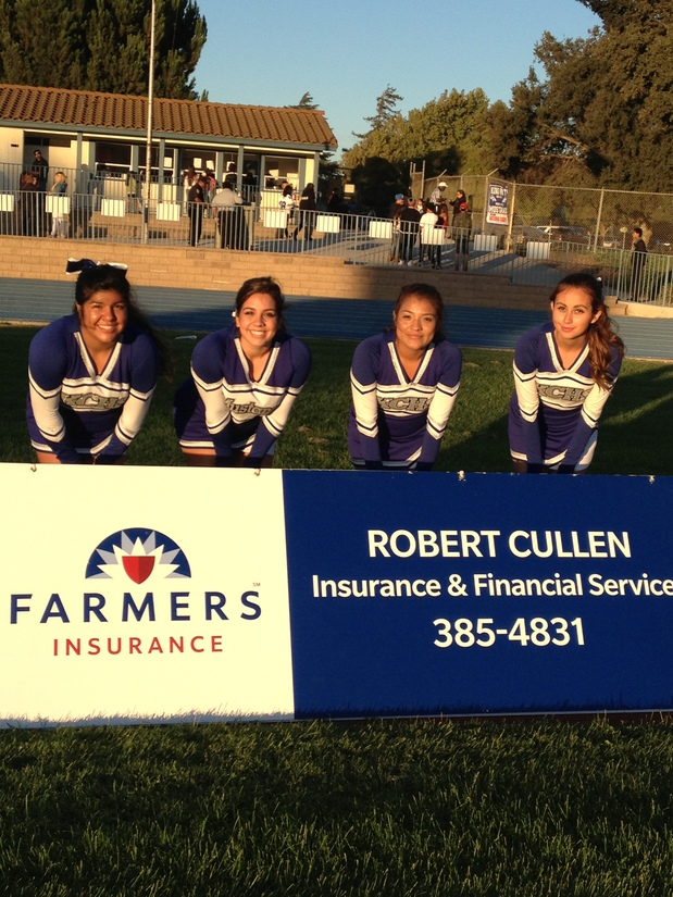 four cheerleaders standing behind farmers sign