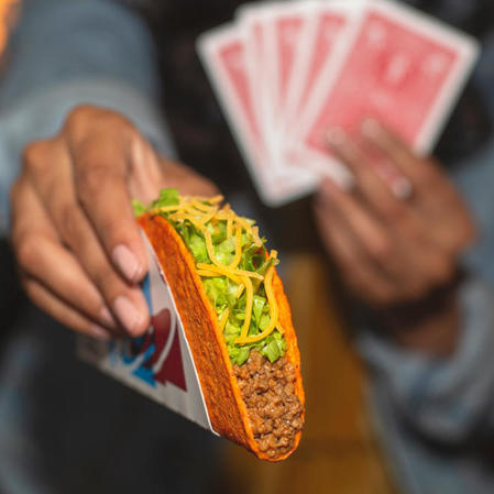 A person holding red playing cards in one hand while offering a Taco Bell Doritos® Loco Taco with the other.