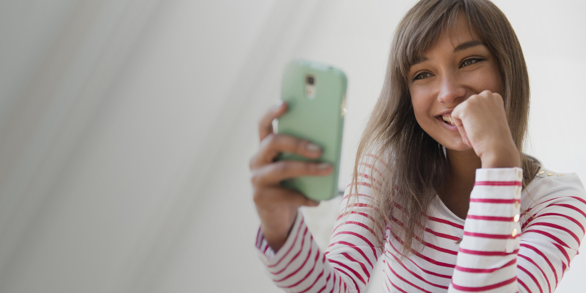 Photo of a young woman smiling at her Altice Mobile connected smart phone