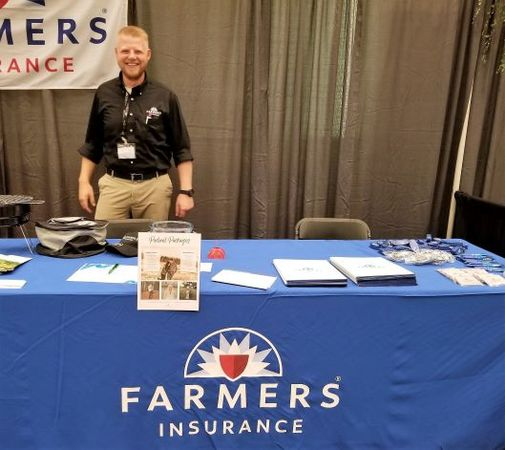 Agent Nicholas posing behind of farmers booth.