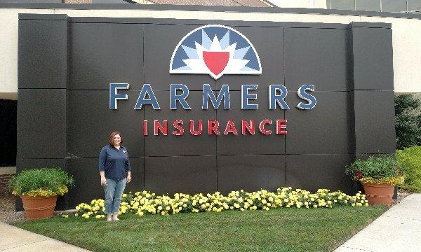 Agent Jannell Neill in front of large Farmers Insurance Stone sign