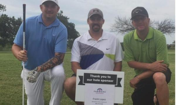Three men in golf attire by sign stating hole sponsorship.