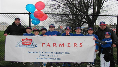 A little-league baseball team hold up a Farmers Insurance banner and smile at the camera