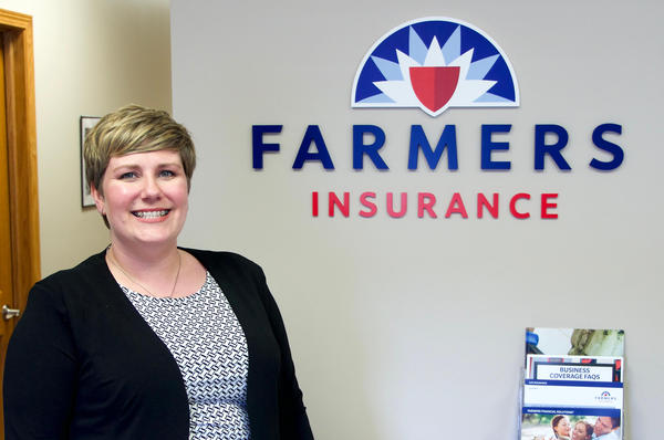person smiling in front of farmers insurance sign