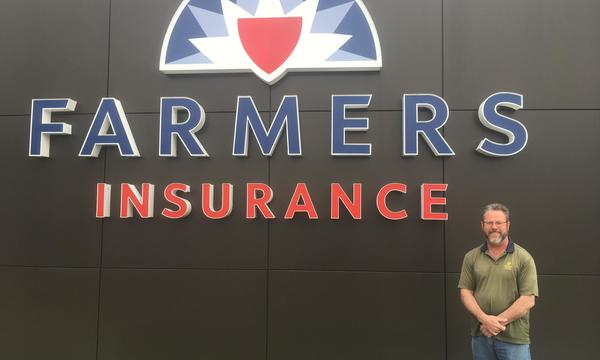 Agent standing in front of Farmers logo