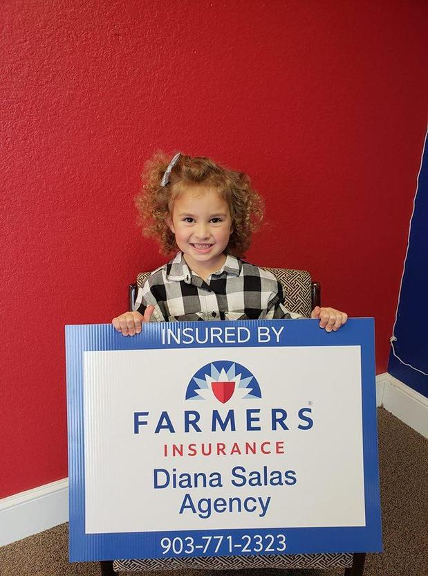 a child behind a farmers sign