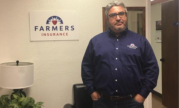 A photo of the Farmers agent next to a Farmers Insurance sign