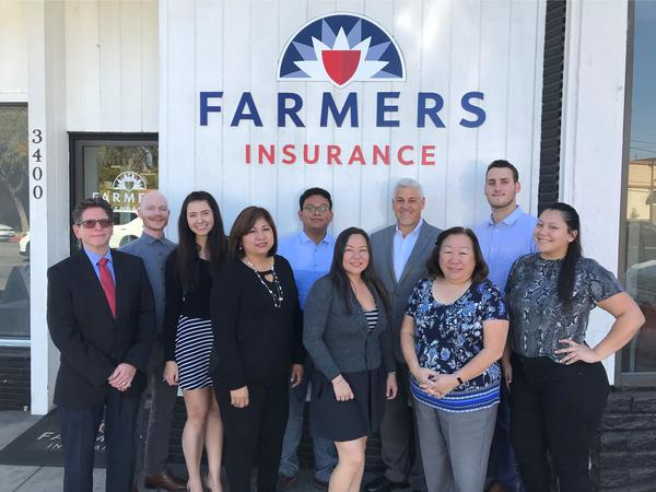 Group photo in front of a Farmers Insurance Banner