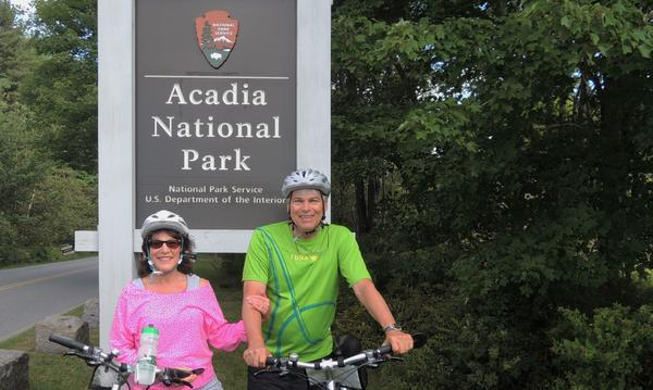 Agent and his wife on bicycles in front of sign for Acadia National Park