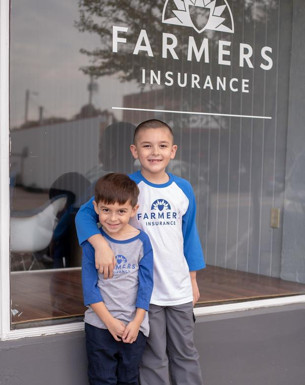 Two children in front of Farmers Sign