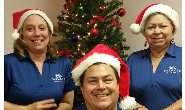 Photo of 3 staff members with Christmas hats in front of a Christmas Tree.