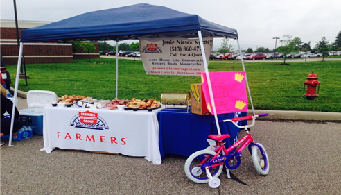 A Farmers booth set up for Paiges Princess Foundation.  It's set up on a grassy lawn with a pink bicycle visible