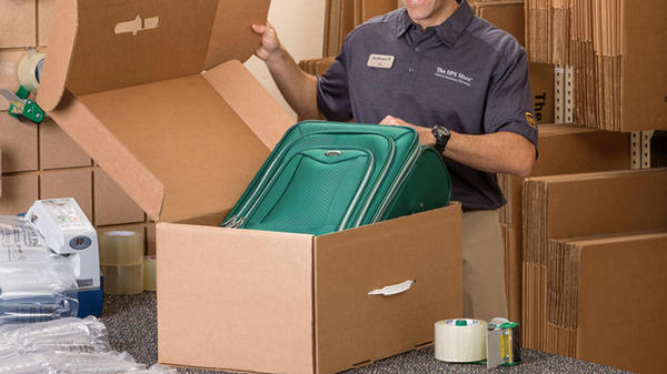 Employee packing luggage into box