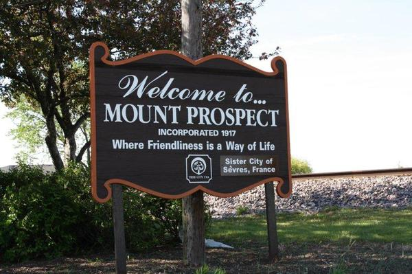 "A sign that reads, ""Welcome to Mount Prospect, Incorporated 1917, Where friendliness is a way of life."""