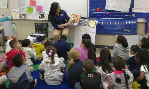 Jessie reads to a classroom of children.
