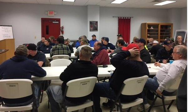 Firefighters sit down to eat chili made by Farmers agents