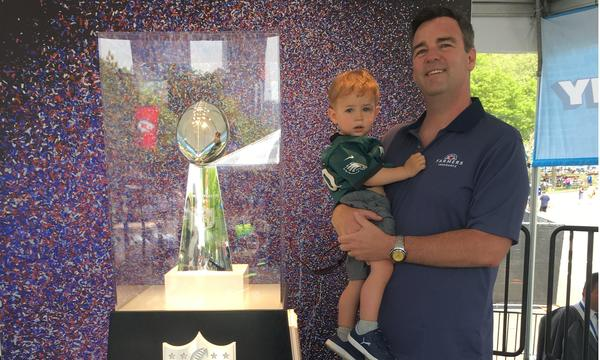 Agent holding child in front of Lombardi Trophy