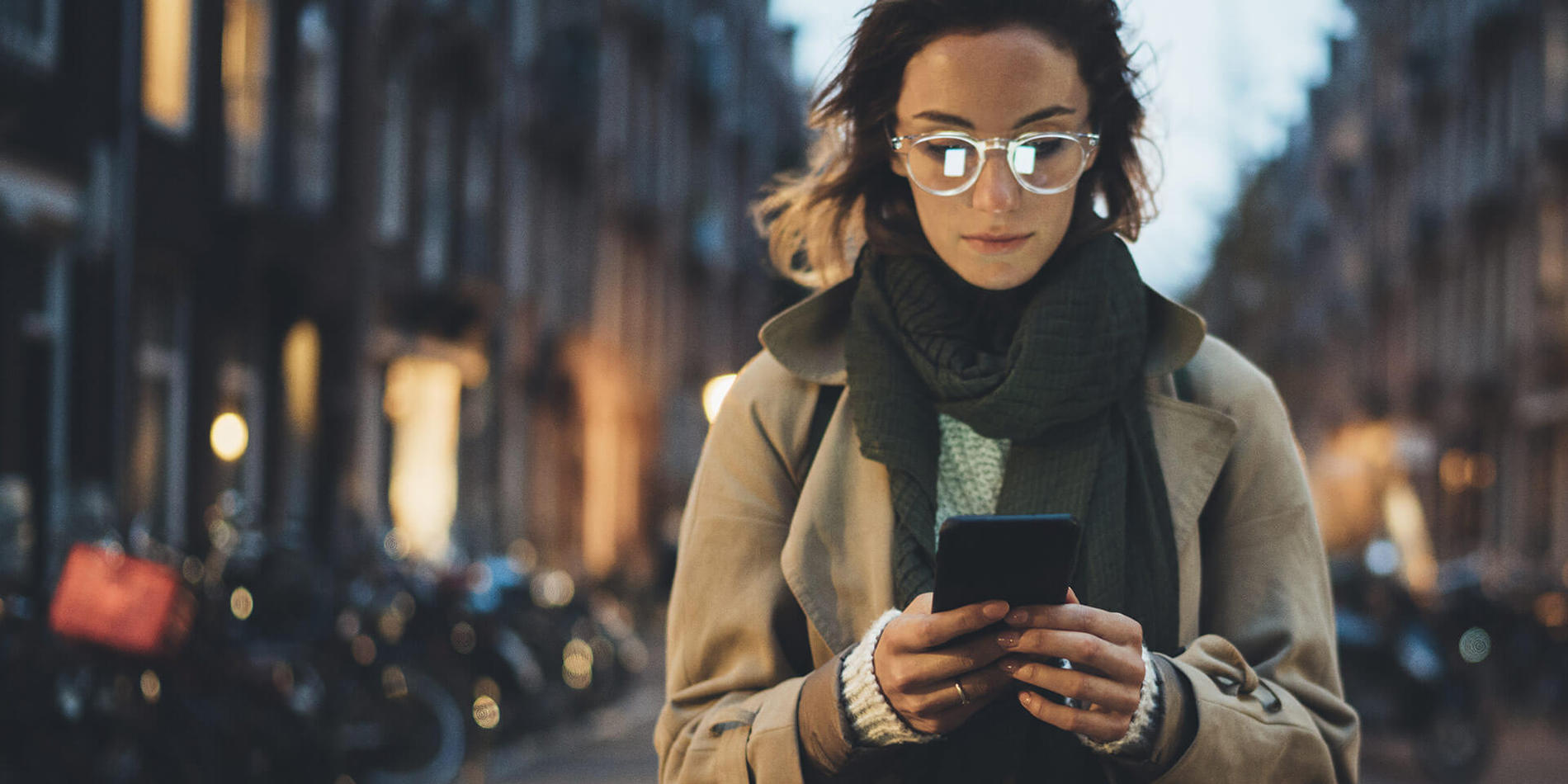 Photo of young woman looking at her Suddenlink WiFi Hotspot connected phone while walking on a city street