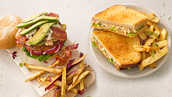 A hamburger with bacon and avocado on a plate next to a chicken mayonaise toasted sandwich with chips.