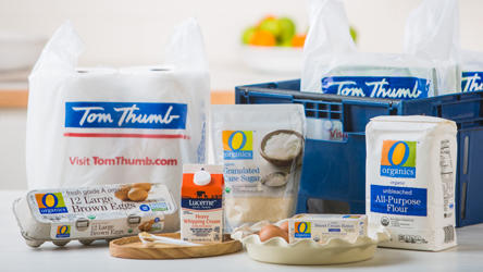 Tom Thumb Grocery bags, delivery box and groceries such as eggs, flour and cream.