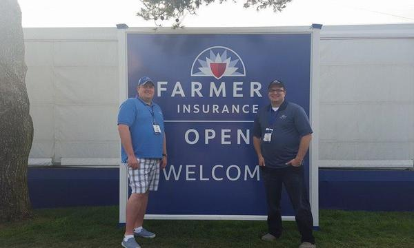 Two men standing in front of a Farmers Insurance Open Welcome Sign.