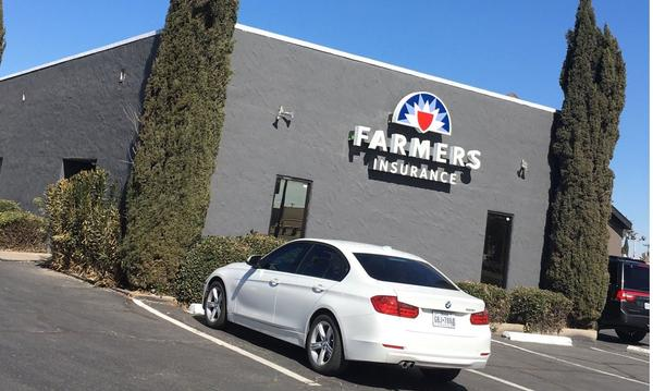 Photo of a car parked outside of a Farmers building.