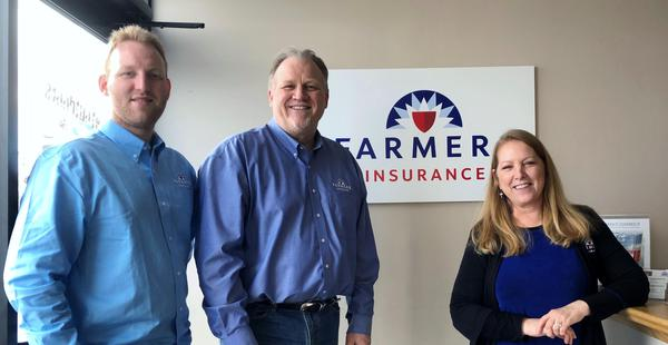 Three people posing for a photo in front of a Farmers Insurance sign.