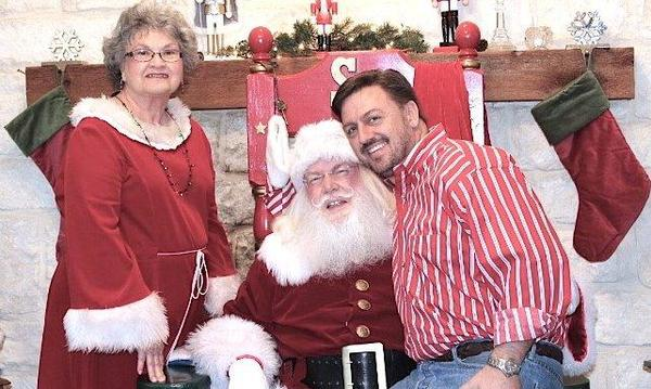 Agent sitting on Santa's lap next to Mrs. Claus