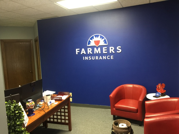 Farmers Insurance full color logo on blue accent wall
