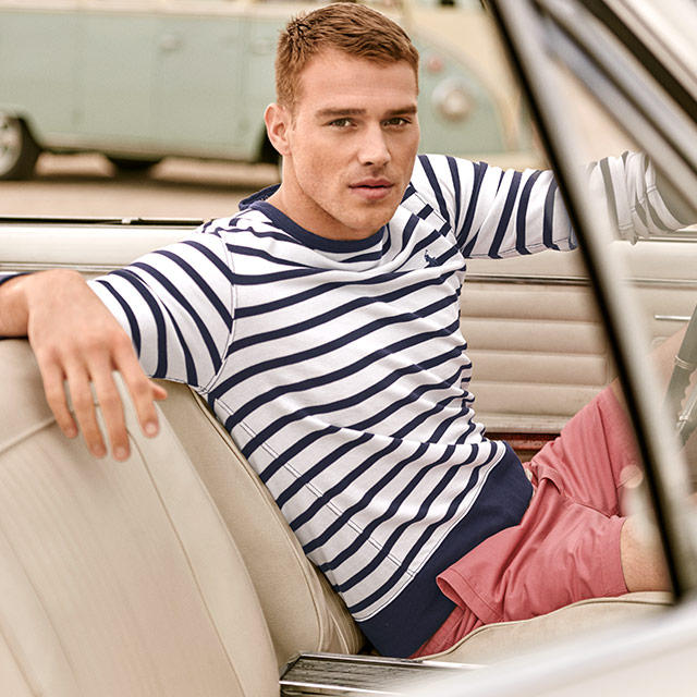 Man with Blue and white striped long sleeve sitting inside a car.