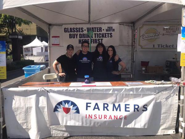 Four people supporting their community volunteering at Farmers booth.