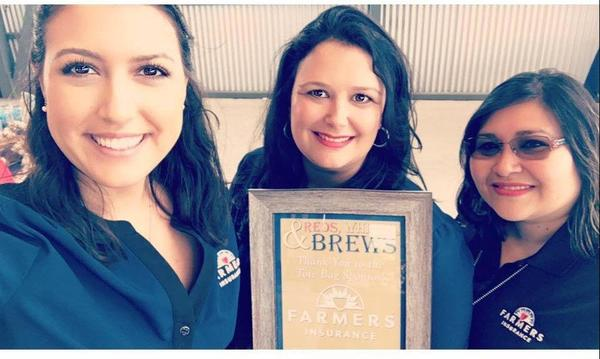 Three women posing for a photo with a plaque.