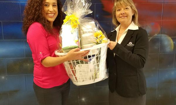 Agent presenting a gift basket to a teacher