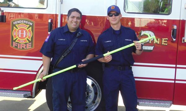 Two firefighters holding a roof hook in front of a fire truck.